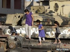 Children play on a destroyed tank