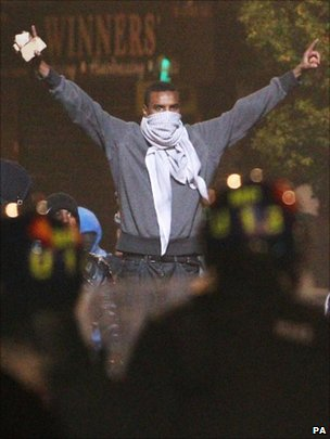Masked rioter with his arms in the air