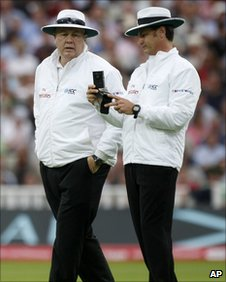 Umpires Steve Davis and Simon Taufel consult their light meters