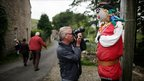 A passer-by takes a photograph of a scarecrow