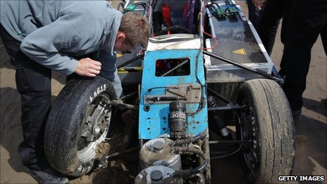 The team examines the damaged suspension 
