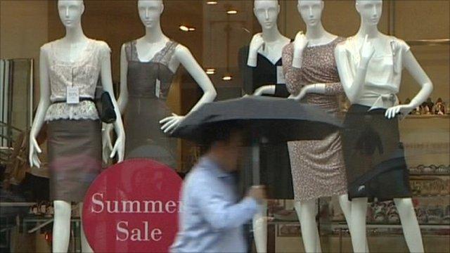Consumer walking in rain past summer sales