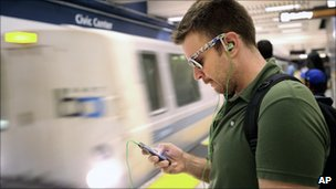 A man uses his iPhone at Civic Centre Station, San Francisco