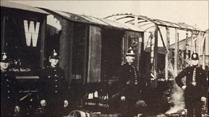 Burnt out wagons guarded by police Photo: Llanelli Library Service