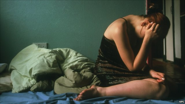 Young woman sits on bed looking depressed