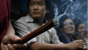 A monk holds incense in Dharmsala, India, Wednesday, 20 July 2011