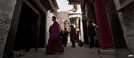Tibetan monk walks past pilgrims at the Labrang monastery in Xiahe, Gansu province, file image
