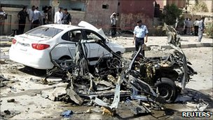 A police officer inspects the wreck of a car bomb in Najaf