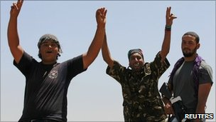 Libyan rebel fighters celebrate as they drive into the coastal city of Zawiya (15 August 2011)