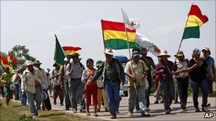 Bolivian indigenous marchers carrying flags on the road from Trinidad to La Paz