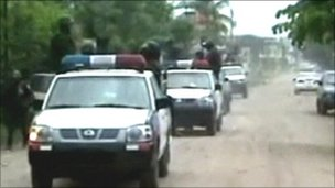 Police vehicles head to the scene of the killings in Honduras