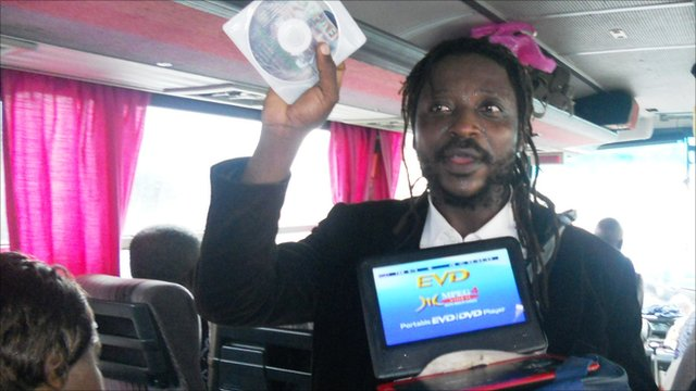 Joe la Conscience sells his music CDs on a bus in Cameroon.