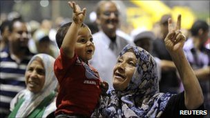 A woman gestures while holding a child during a pro-Gaddafi rally in Green Square, Tripoli, in a picture taken on government-organised tour 15 August 2011,