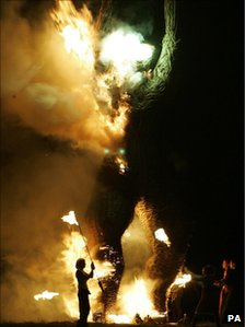 Fire dancers torch a giant Wicker Man at the Wickerman Festival, Kirkcudbright
