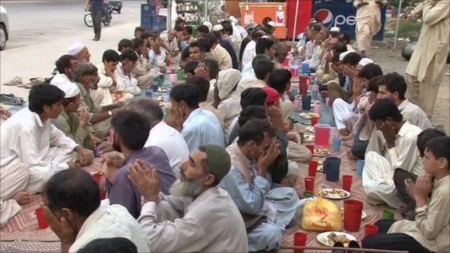 Pakistanis workers breaking their fast to a charity meal - by the side of the road - during the month of Ramadan.