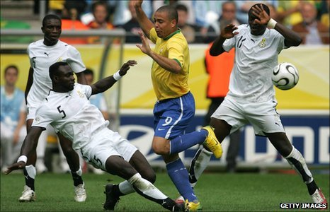 Brazil's Ronaldo (in yellow) is tackled by Ghana's John Mensah (number 5) as Sulley Muntari (number 11) takes evasive action
