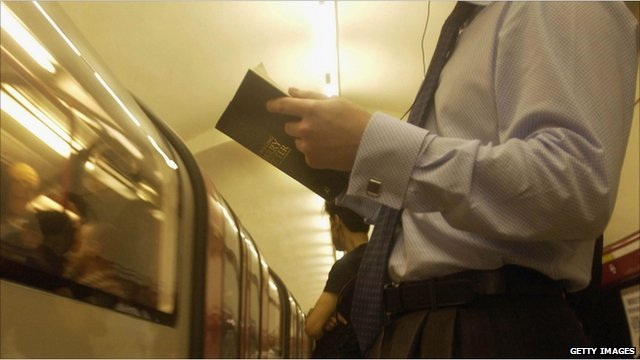 A passenger on the London underground reads a Harry Potter book