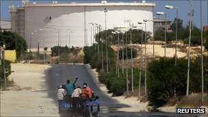 A truck carrying Libyan rebel fighters drives towards the oil refinery in Zawiya, Libya, 17 August 2011