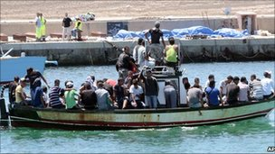 Migrants on a boat sailing past the Lampedusa port