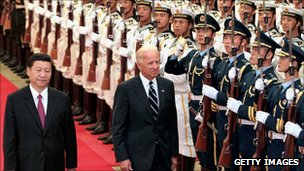 Chinese Vice-President Xi Jinping accompanies US Vice-President Joe Biden (R) to view an honour guard during a welcoming ceremony in Beijing