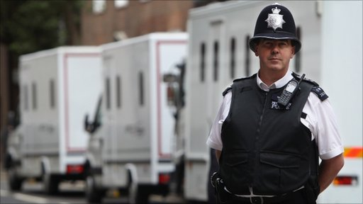 A police officer stands in front of a line of Serco Vans outside Westminster Magistrates court
