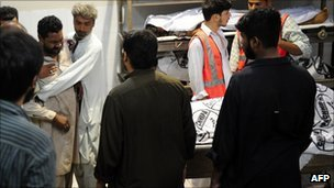 A Pakistani relative (2L) comforts a mourner after the killing of a victim of the shooting, inside a morgue at a local hospital in Karachi on August 18, 2011.