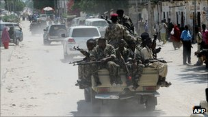 Somali army soldiers ride in the back of a pick up truck as they make their way to the northern part of Mogadishu on 17 August 2011