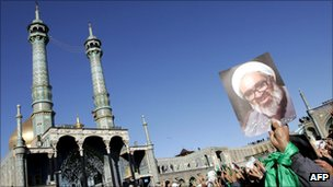 Iranian holds picture of Grand Ayatollah Montazeri at his funeral procession in the holy city of Qom