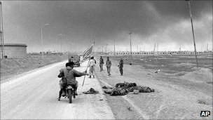 Iranian soldiers ride a motorcycle past the bodies of dead Iraqi soldiers at Faw, 1986