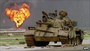 Oil well set alight by retreating Iraqi forces burns in background as Iraqi tank stands abandoned