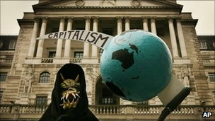 A grim reaper figure holds a globe pierced by the scythe of capitalism in front of the Bank of England during a protest on 13 October, 2008
