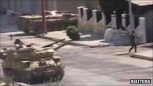 A still allegedly showing a Syrian soldier walking near a tank in Syria&#039;s city of Hama. Photo: August 2011