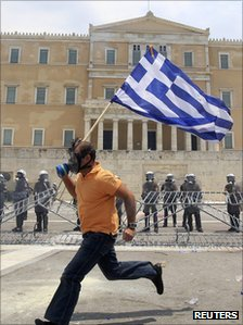 A demonstrator runs with the national Greek flag in front of the riot police during a protest outside the parliament in Athens 29 June 2011.