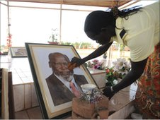 A woman cleans a picture of John Garang in the mausoleum