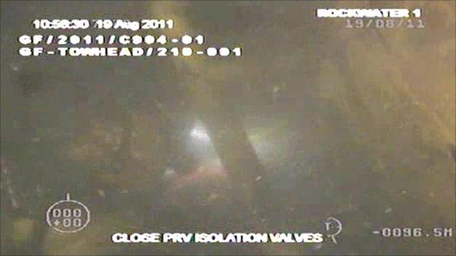 diver closes valve to stop leak