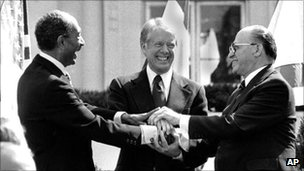 Egyptian President Anwar Sadat (left) with US President Jimmy Carter (centre) and Israeli PM Menachem Begin clasp hands after signing the peace treaty on 26 March 1979 at the White House