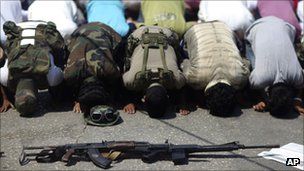Rebel fighters, foreground, pray during Friday prayers in the rebel-held town of Benghazi, Libya, Friday, Aug. 19, 2011