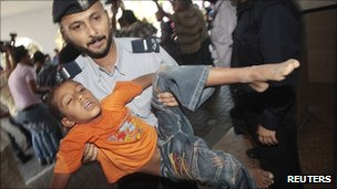 A policeman carries a wounded boy into a hospital following an Israeli air strike in Gaza City on 20 August 2011