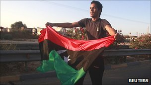 A man waves a Libyan rebel flag in the town of Maia