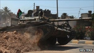 A Libyan rebel tank drives through Maya, 21 August
