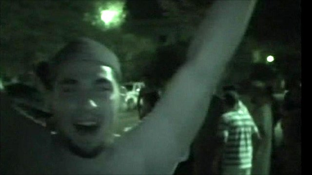 Night vision image: A man facing the camera cheers. In the background, people are standing at the side of a road.