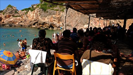 Tourists enjoy lunch in a small restaurant at the Cala de Deya in Palma de Majorca, Spain