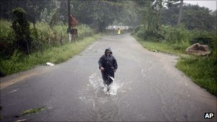 A man wades through a flooded street after hurricane Irene hit the area in Naguabo, Puerto Rico, 22 August 2011