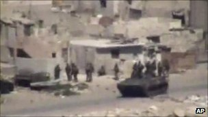 This image taken from amateur video made available on 17 August 2011 purports to show armoured vehicles and troops as they take up positions in Latakia, Syria
