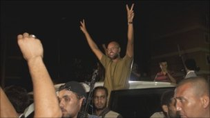 Col Gaddafi's son, Saif al-Islam, waves to troops loyal to his father in Tripoli, 22 August