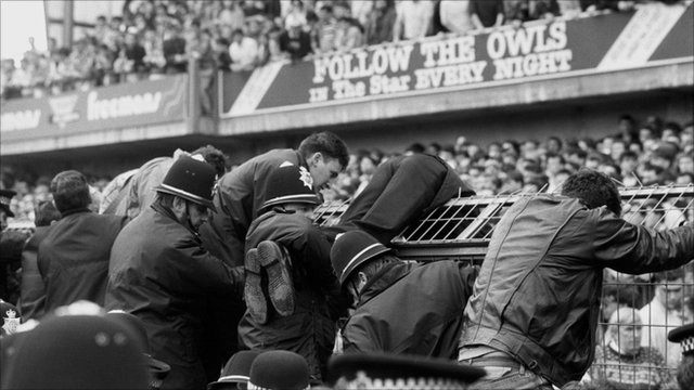 Police help fans over the fencing during the Hillsborough football disaster