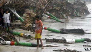 People walk along a battered beach in Nagua on  the northern coast of the island of Hispaniola, which the Dominican Republic shares with Haiti