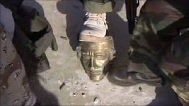 Rebels stand on Gaddafi statue