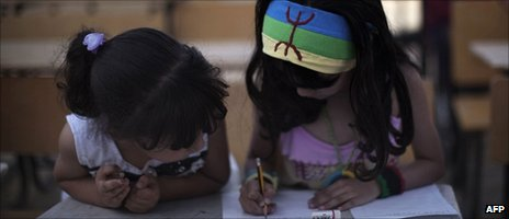 A Libyan girl from the Amazigh community wears a headband sporting the traditional symbol of peace as she attends a class in her ancient language  of Tamazight in Jadu in eastern Libya in July 2011