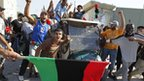 Libyan rebel fighters celebrate entering Colonel Gaddafi's compound in Tripoli.